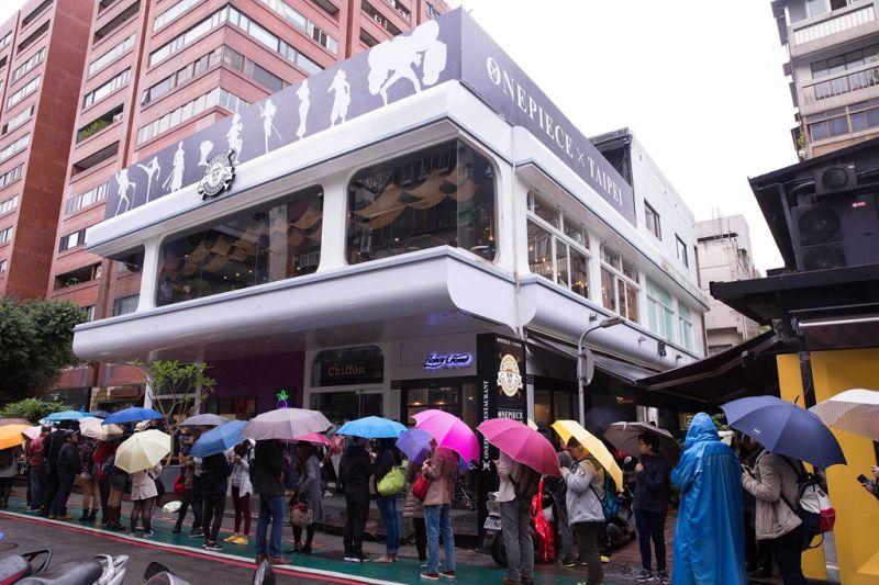 熱血粉絲不畏雨天撐著傘排隊搶先入座。(《台灣航海王》餐廳提供)